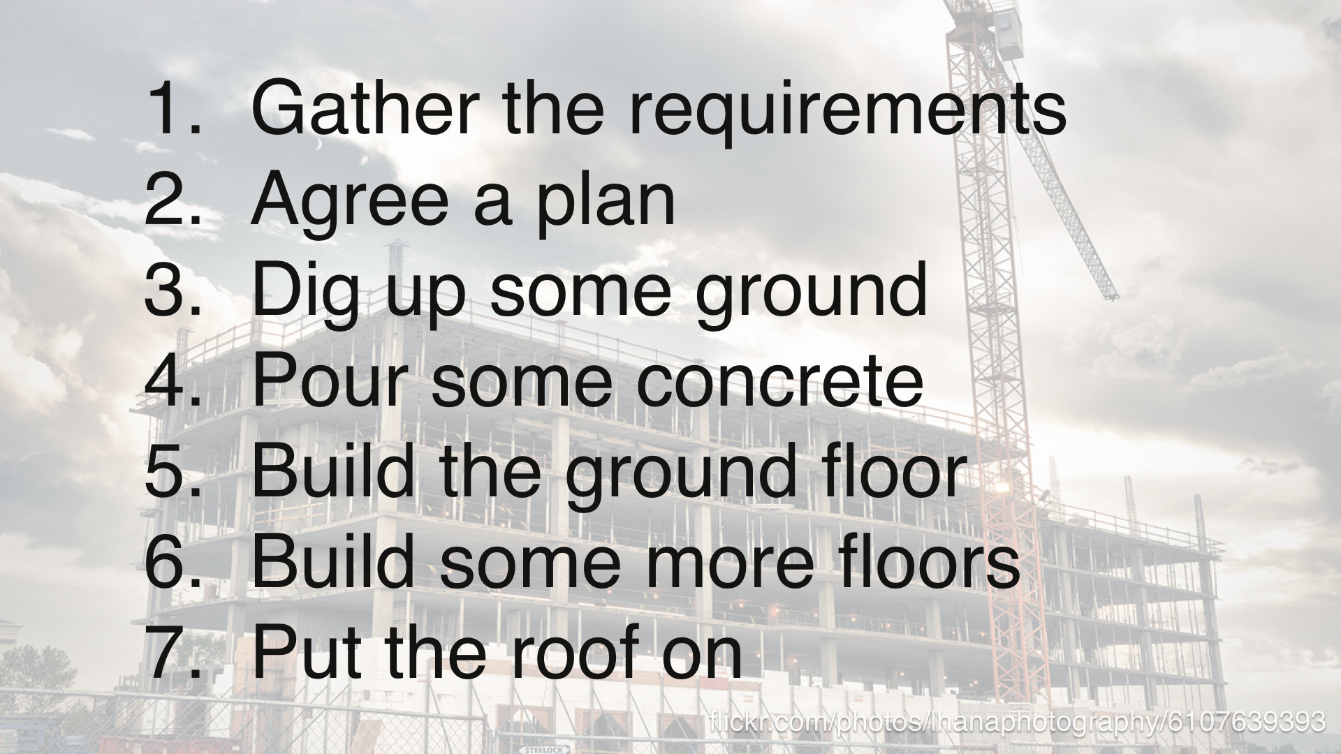 1. gather the requirements. 2. agree a plan. 3. dig up some ground. 4. pour some concrete. 5. build the ground floor. 6. build some more floors. 7. put the roof on