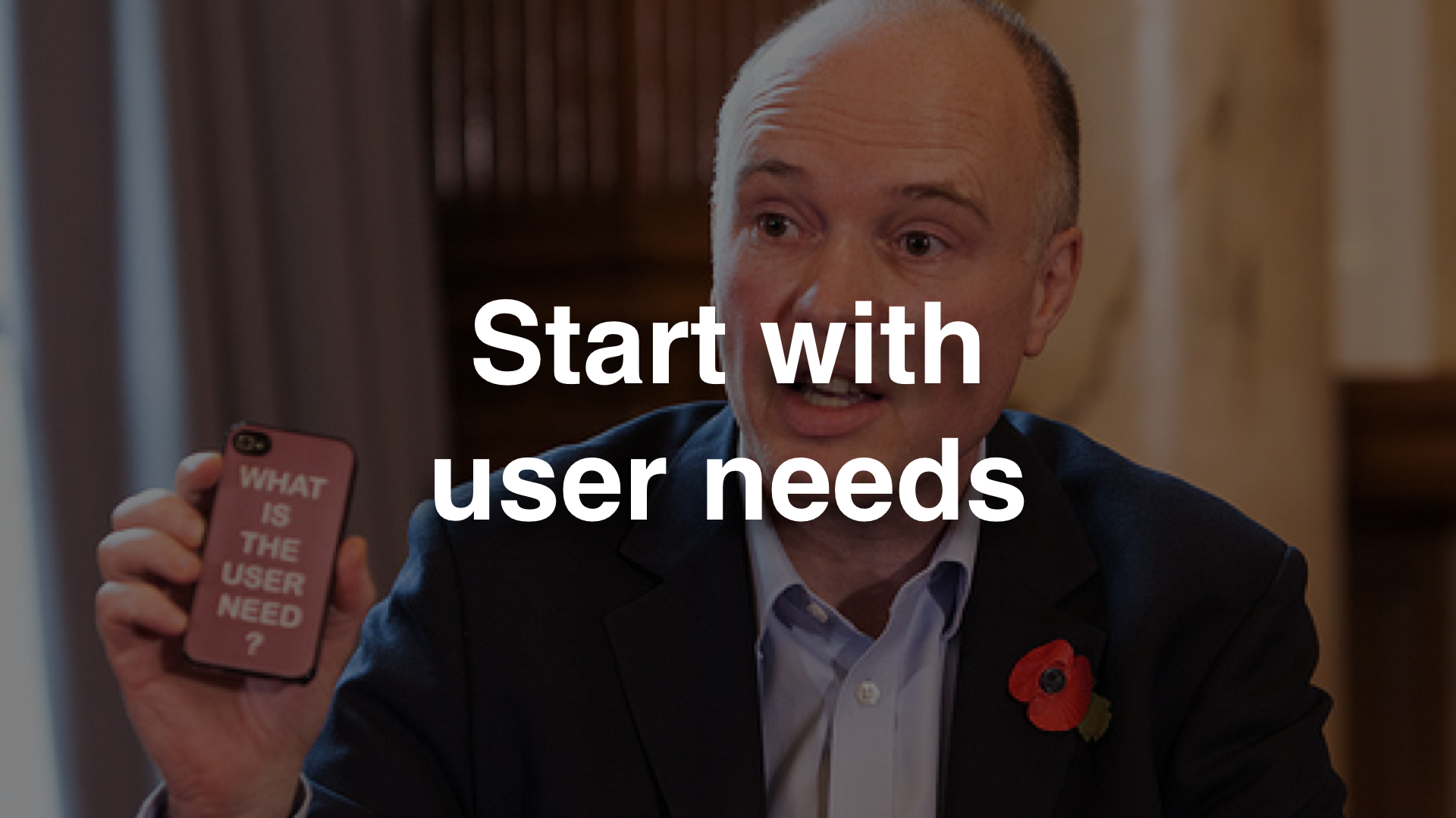 """Start with user needs"" - photo of Liam Maxwell holding a mobile phone that says ""what is the user need?"""
