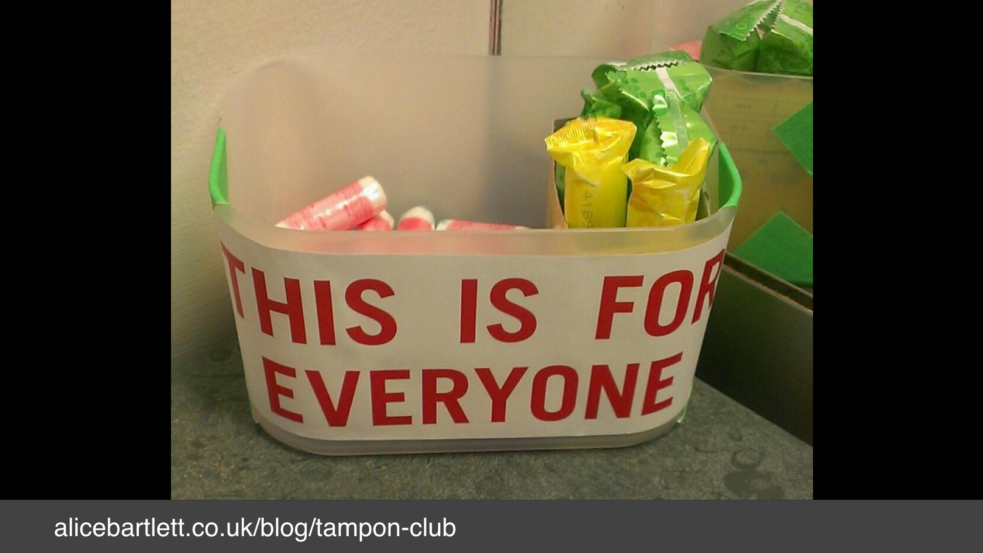"A photo of a basket of tampons with a label: ""this is for everyone"""